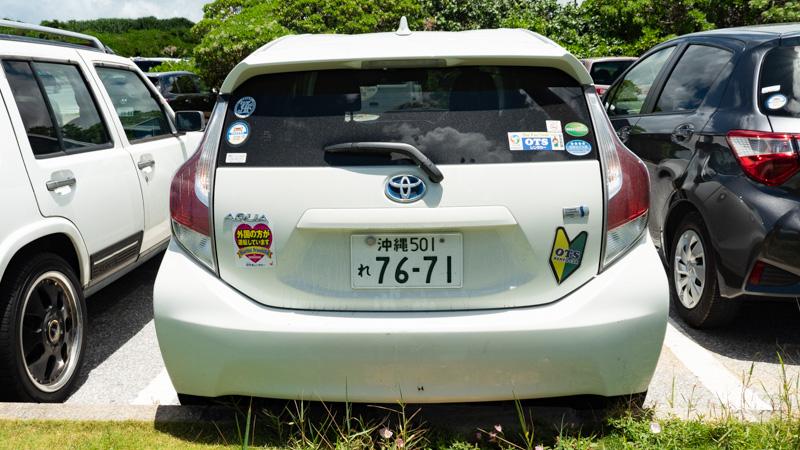 レンタカーのステッカーや初心者マークが貼られたレンタカー(トヨタ アクア)