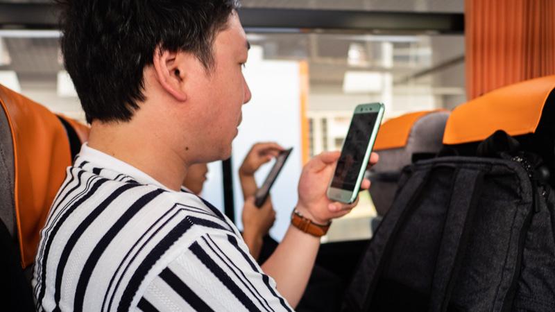 空港リムジンバス内で携帯電話を操作している様子
