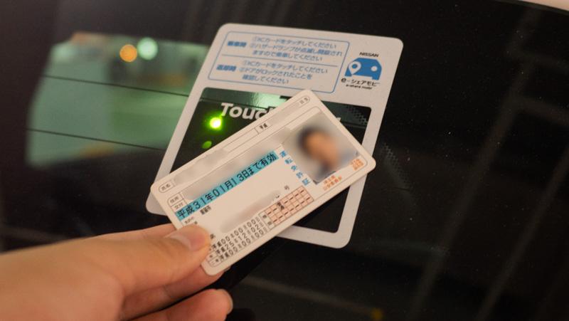 日産 e-シェアモビの車両に自身の免許証をかざして貸出手続きを行っている様子