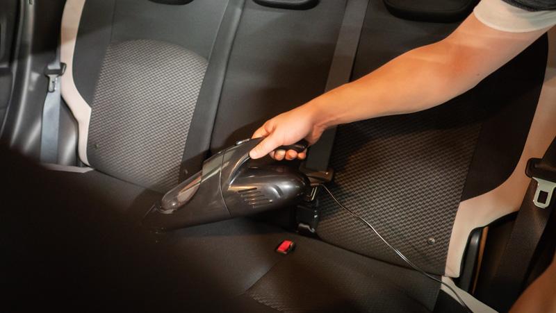 日産e-シェアモビの日産ノートに備え付けられている車載掃除機で後部座席を掃除している様子